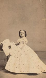 Photo portrait of Lavinia Bump, 1863, wearing short sleeved patterned dress and styled hair, side view near table, but Lavinia faces camera. Courtesy, Barnum Museum
